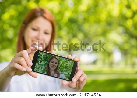 Pretty redhead taking a selfie on her phone in the park on a sunny day - stock photo