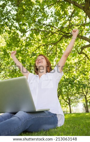 Pretty redhead using her laptop in the park and cheering on a sunny day - stock photo