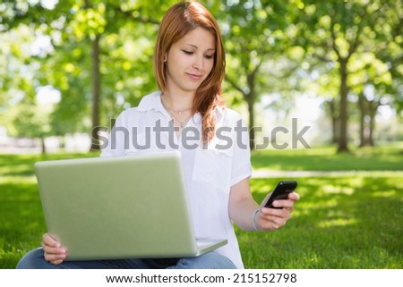 Pretty redhead using her laptop while texting in the park on a sunny day - stock photo