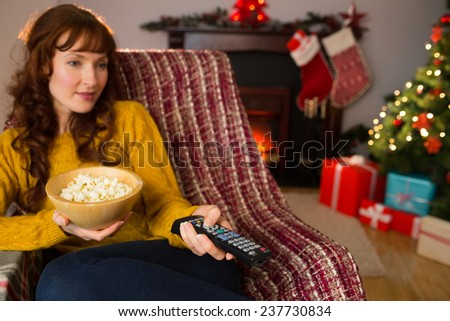 Pretty redhead watching television on couch at christmas at home in the living room - stock photo