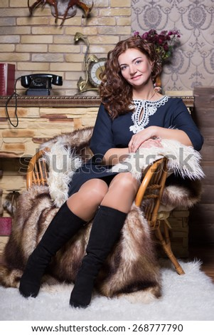Pretty redhead woman in blue dress and black boots sitting near the fireplace - stock photo