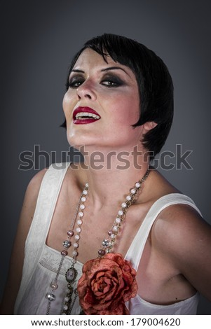 Pretty Retro posing lady,  flapper dress, Girl dreaming beautiful young woman from roaring 20s looking at camera.  vintage twenties - stock photo