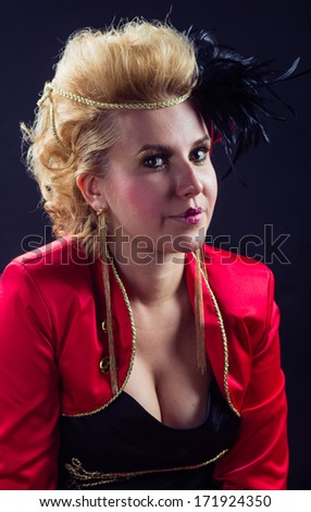 Pretty ringmaster woman with red jacket and black plume, isolated on black background