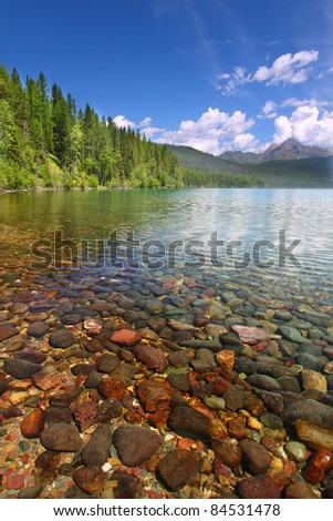 Pretty rocks seen through the crystal clear waters of Kintla Lake in Glacier National Park - USA - stock photo
