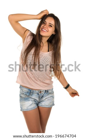 Pretty Romanian brunette in a pink tee shirt and denim shorts - stock photo