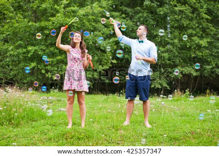 Pretty romantic couple in love having fun with soap bubbles in the nature