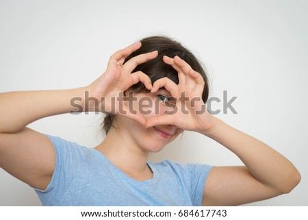 Pretty romantic young woman making a heart gesture with her fingers showing her love and affection with a happy tender smile