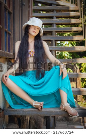 pretty sad girl sitting on village staircases - stock photo