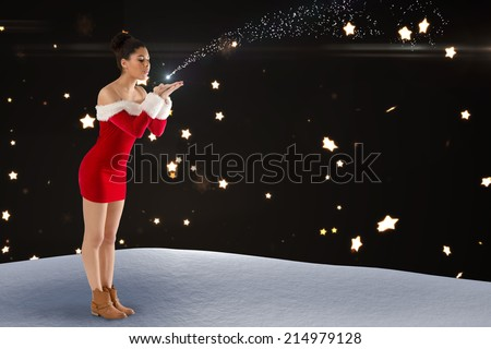 Pretty santa girl blowing over her hands against bright star pattern on black