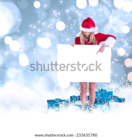 Pretty santa girl holding poster against white glowing dots on blue - stock photo