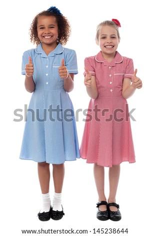 Pretty school girls gesturing thumbs up - stock photo