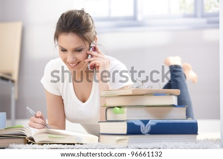Pretty schoolgirl laying on floor, studying, chatting on mobile phone, smiling.?