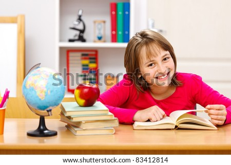 Pretty schoolgirl reading in classroom. Earth globe and whole apple on other stacked books