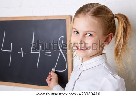 Pretty schoolgirl standing near blackboard with piece of chalk and smiling - stock photo