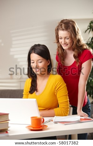 Pretty schoolgirls learning at home looking at laptop at table smiling.? - stock photo