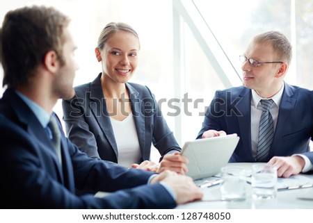 Pretty secretary looking at one of partners while planning work at meeting - stock photo