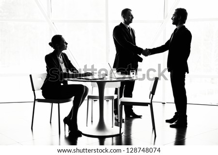 Pretty secretary looking at two businessmen handshaking at meeting