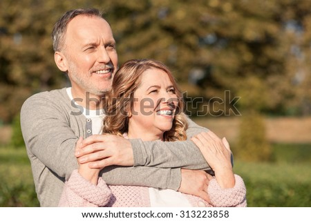 Pretty senior husband and wife are standing in park and embracing. They are looking forward happily and smiling - stock photo