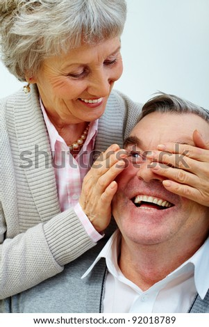 Pretty senior wife closes husband's eyes by hands