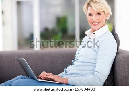 pretty senior woman at home using laptop - stock photo