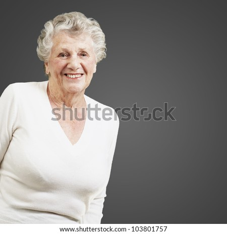 pretty senior woman smiling against a black background