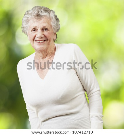 pretty senior woman smiling against a nature background - stock photo