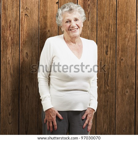 pretty senior woman smiling against a wooden background - stock photo