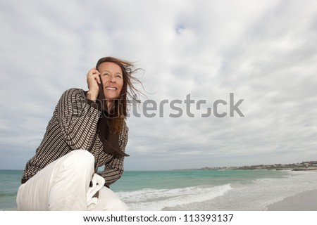 Pretty senior woman with natural happy look at windy stormy weather at ocean, isolated with sea and dark cloudscape as background and copy space.