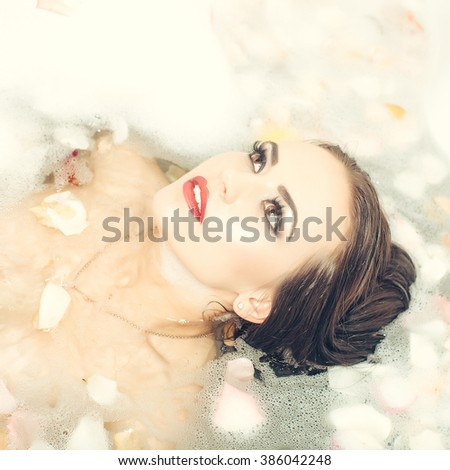 Pretty sensual brunette young woman with wet hair and bright makeup lying in bath tub full of water with foam and rose flower petals, square picture - stock photo