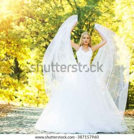 Pretty sensual thoughtful young bride girl with long blonde hair in beautiful white wedding dress standing outdoor on autumn natural background, vertical picture