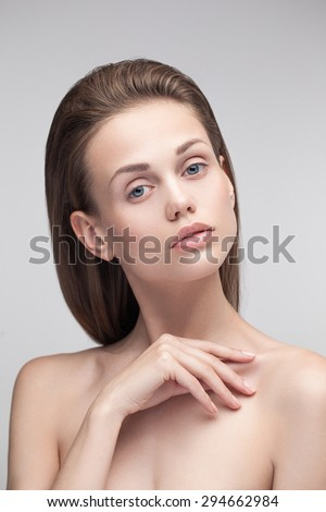 Pretty sensual young girl posing in studio looking at camera. White perfect skin with natural fresh makeup, hazel straight hair, blue eyes, nude nails. - stock photo