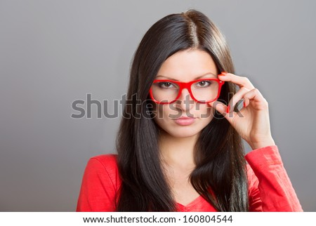 Pretty serious girl looking over glasses, studio shot on gray background nails - stock photo