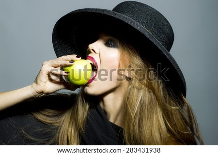 Pretty sexual girl in retro black hat with bright make up biting fresh green apple standing on gray background copyspace, horizontal picture - stock photo