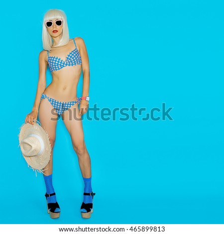 Pretty Sexy Blonde in a retro polka Dot Swimsuit on a blue background. Hot Summer Style