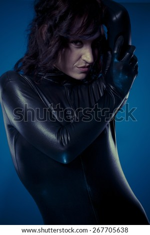 Pretty sexy brunette in black latex bodysuit tight and wild poses - stock photo