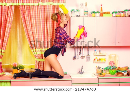 Pretty sexy pin-up girl cleans her glamorous pink kitchen. Retro style. Fashion. - stock photo