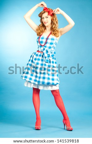Pretty sexy redhead Pin Up girl in  checkered dress and red stockings adjusts the bow on her head - stock photo