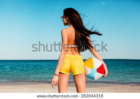 Pretty sexy sportive tan woman playing ball  on the summer beach . Wearing yellow shirts, colorful  top and cool glasses. - stock photo