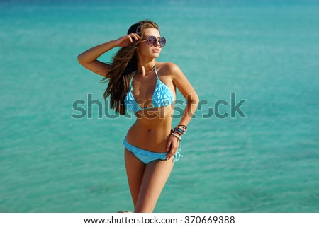 Pretty sexy woman in blue bikini posing against blue ocean water. Attractive woman enjoying sun at vacation - stock photo