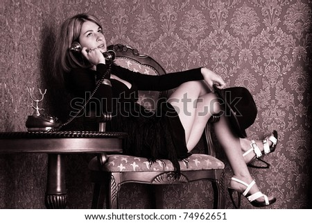 Pretty sexy woman is sitting and talking on an old telephone. Retro style