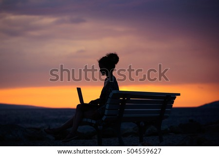pretty sexy woman or girl with laptop or computer sits on bench outdoor over dark twilight sky with clouds on beach with sea or ocean water on evening natural background