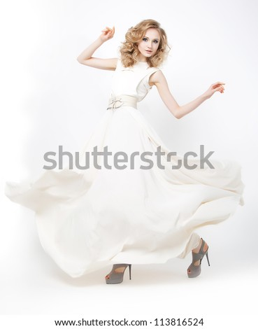 Pretty sexy young woman blonde with flying dress running. Studio shot. Series of photos - stock photo