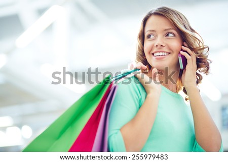 Pretty shopper with paperbags speaking on the phone