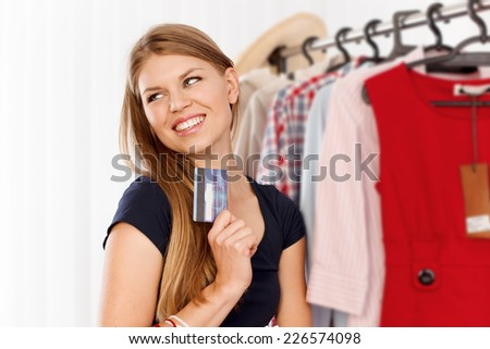 Pretty shopping woman waiting for money spending. Young attractive female buyer standing at clothing rack with credit card.  - stock photo