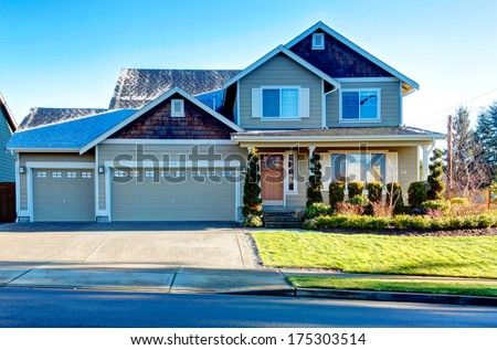 Pretty siding house with colomn porch  and attached garage. The green lawn with flower bed and trimmed hedges - stock photo