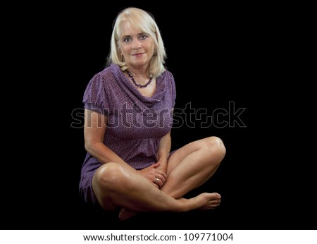Pretty sixty year old woman posing in a lavender dress. - stock photo