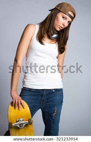 Pretty skater girl leaning on skateboard - stock photo