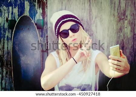 Pretty skater girl taking a selfie - stock photo