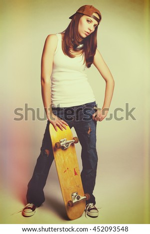 Pretty skater girl with skateboard - stock photo