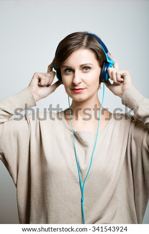 Pretty slim girl listening to good music with headphones, studio photo on isolated gray background - stock photo
